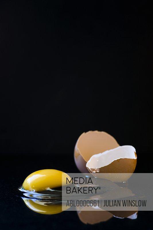 Broken egg on black background