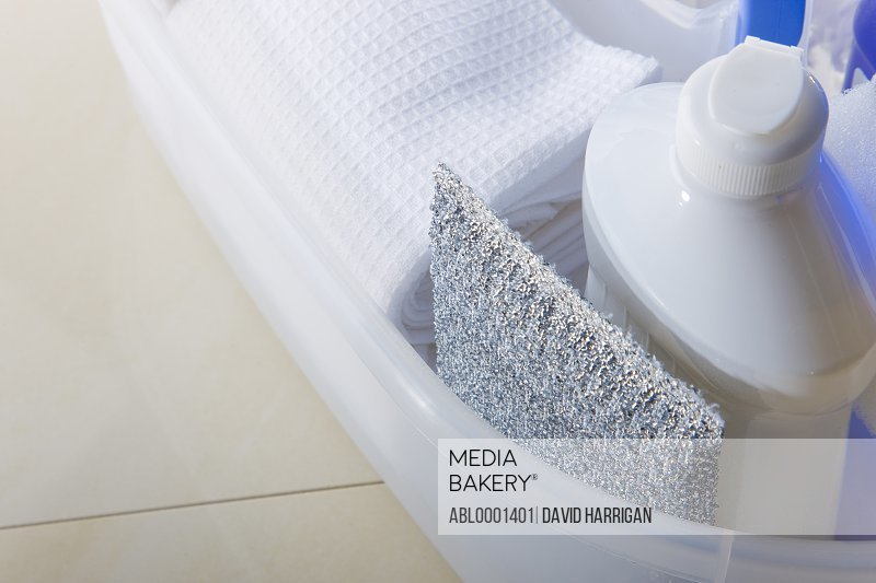 Close up of a cleaning caddy filled with cleaning products on a ceramic floor