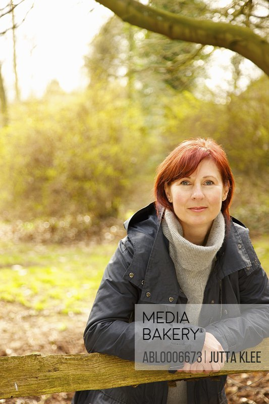 Woman Leaning against Wooden Fence Outdoors