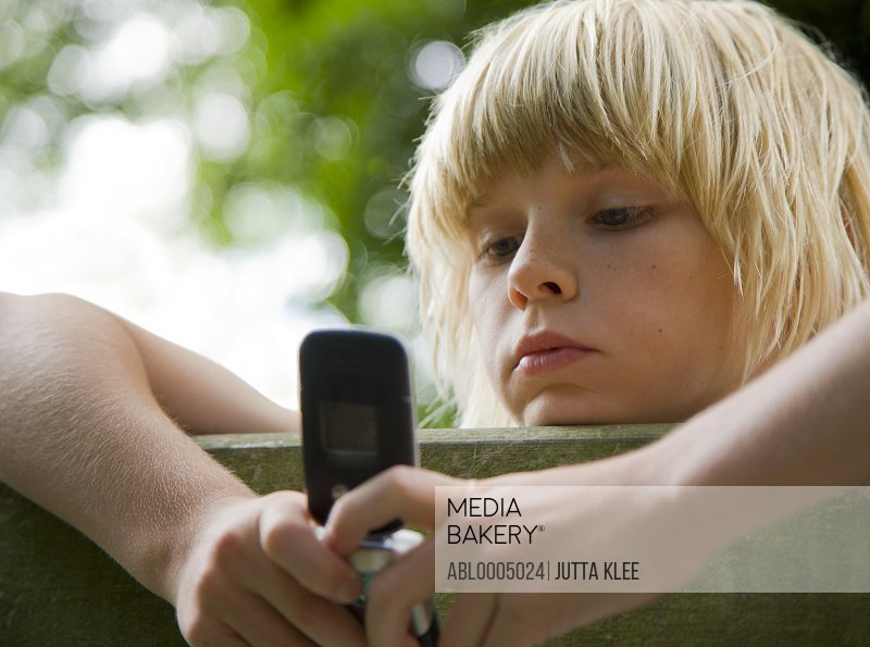 Young boy with arms over wooden fence holding and looking at cell phone