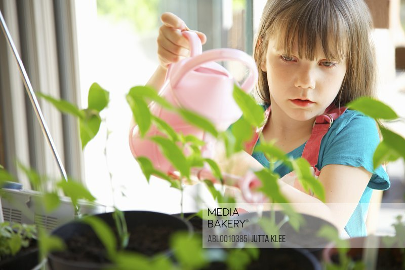 Young Girl Watering Plants with Pink Watering Can