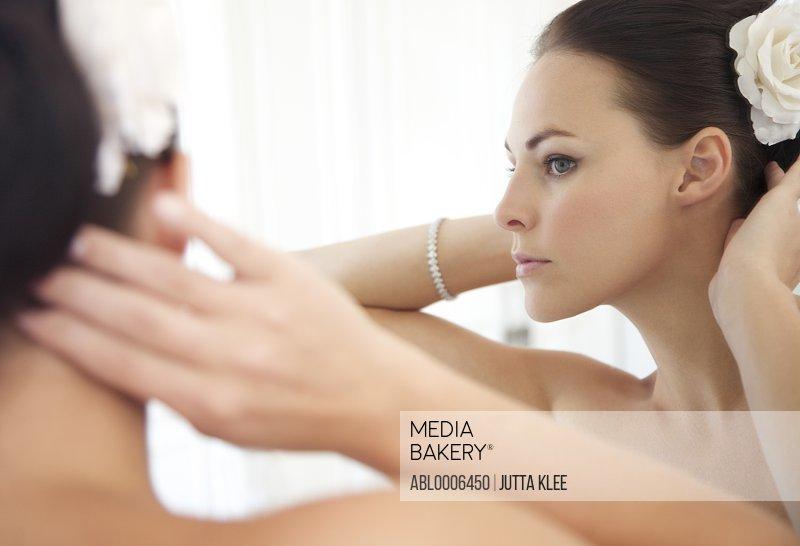 Mirror Image of Woman Adjusting Hair