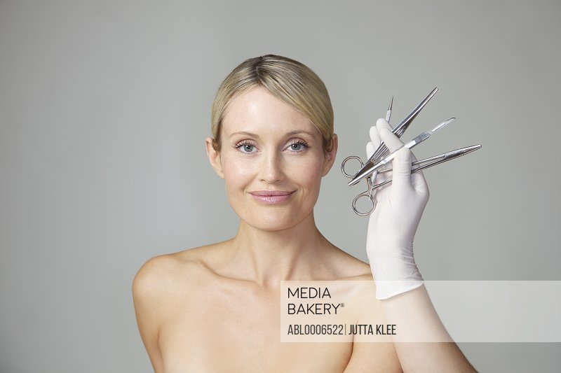 Doctor's Hand Holding Surgical Instruments in front of Woman's Face