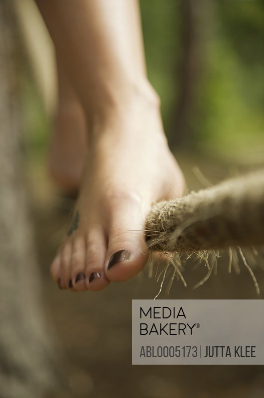 Close up of a woman feet walking on tightrope