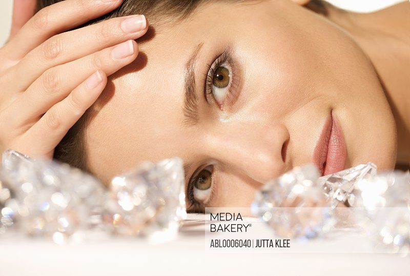 Close up of a young woman lying behind large diamonds