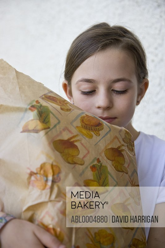 Young girl carrying a brown paper bag