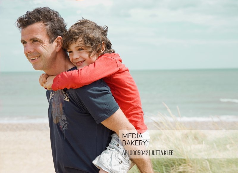 Young boy riding piggyback on his father shoulder on a beach