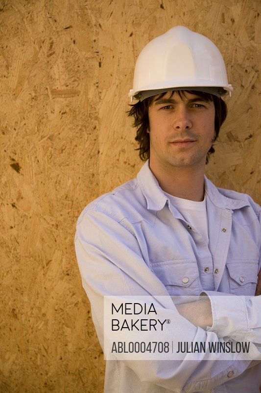 Portrait of a young man wearing hard hat at construction site