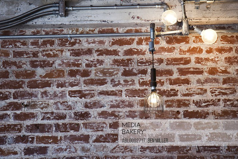 Illuminated Light Bulbs Hanging in front of Brick Wall