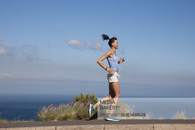 Woman Running along Road by Ocean