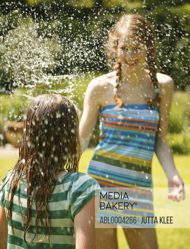 Portrait of teen girl spraying little sister with water