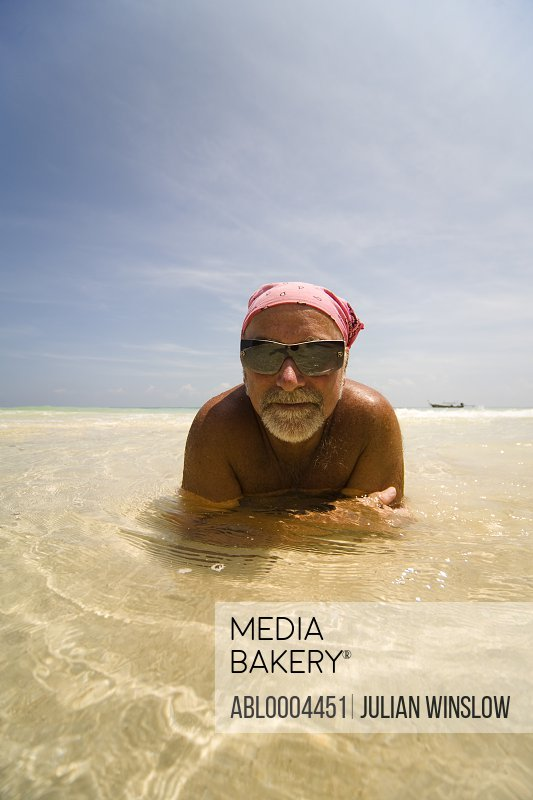 Portrait of man lying down in crystal clear sea