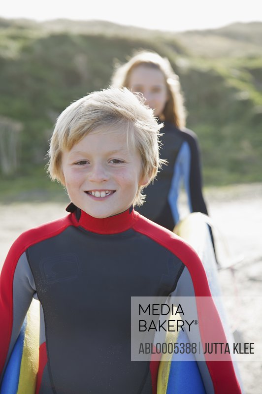 Smiling boy in a wetsuit carrying a surfboard with a girl