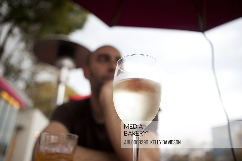Man Sitting at Outdoor Bar with Glass of White Wine in Foreground