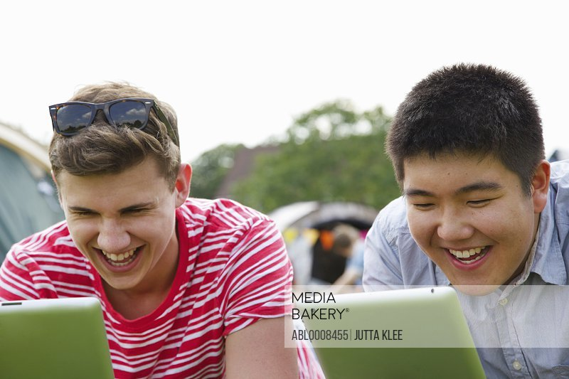 Laughing Teenage Boys Using Tablets