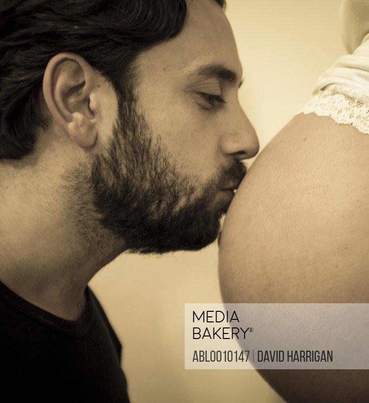 Man Kissing Woman Pregnant Belly