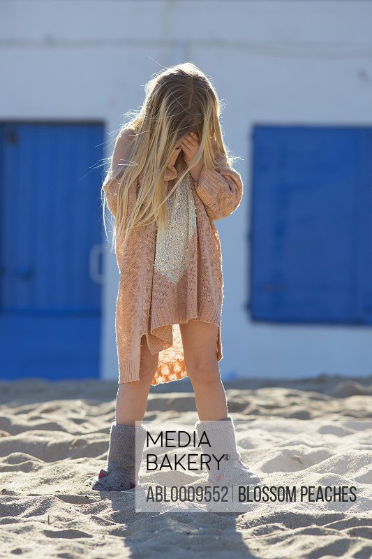 Young Girl Standing on Beach Covering Her Face