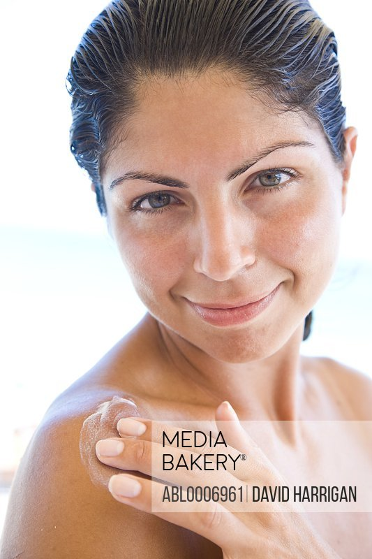 Smiling Woman Applying Body Lotion on Shoulder