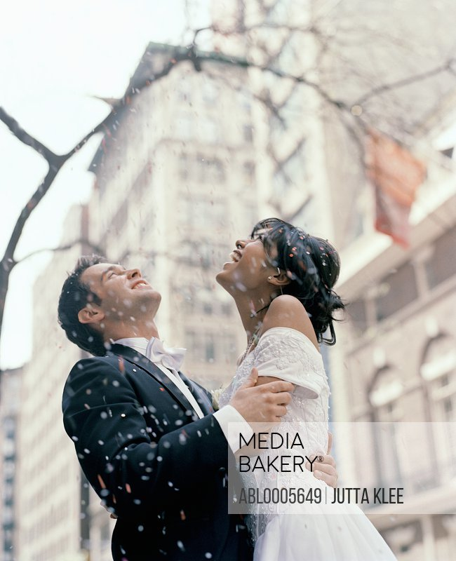 Bride and groom standing under a confetti shower in a New York street