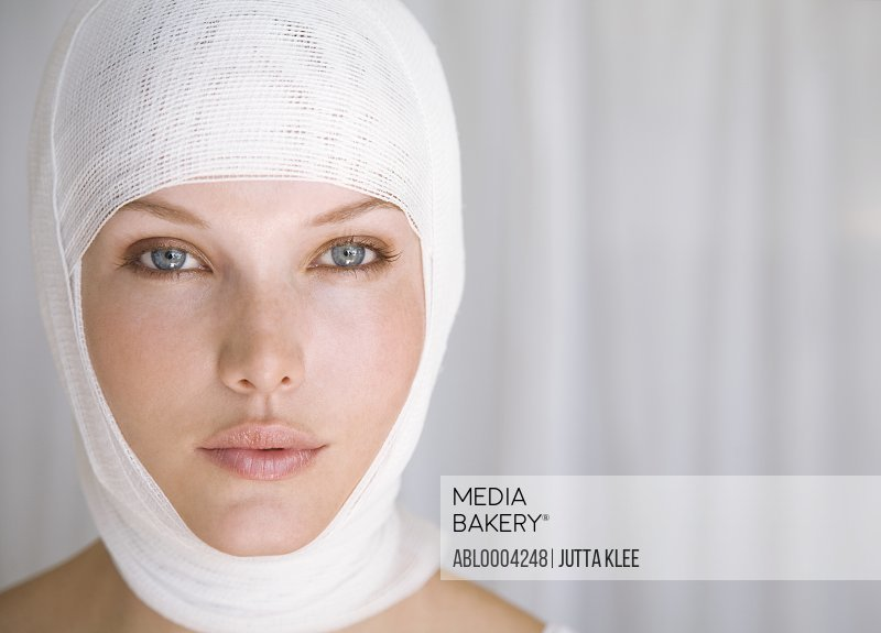 Close up of woman face with bandages wrapped around head