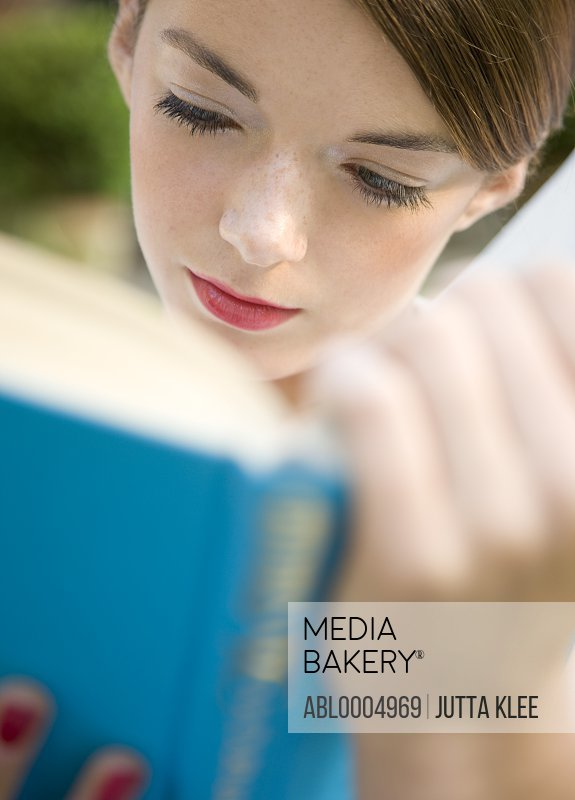 Close up of a teenaged girl reading a book