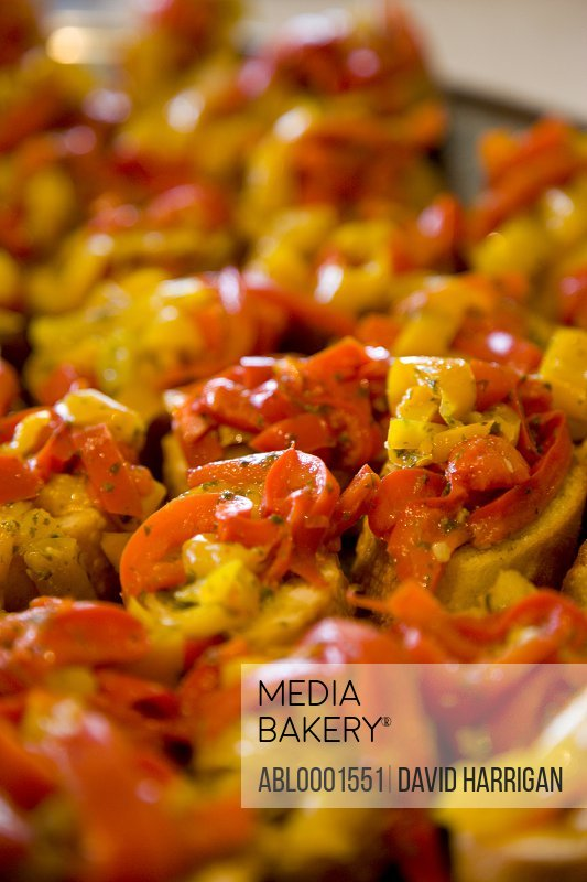Close up of red and yellow peppers crostini