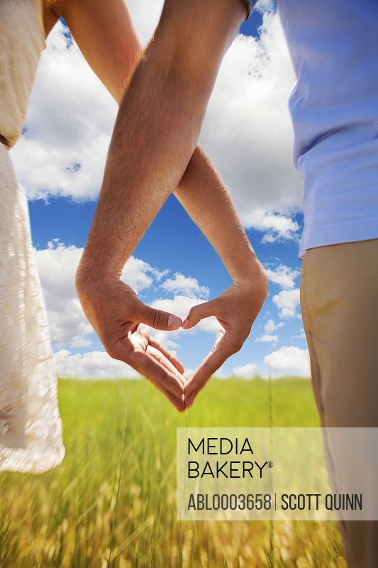 Couple Making Heart Shape with Hands in Field, Cropped view