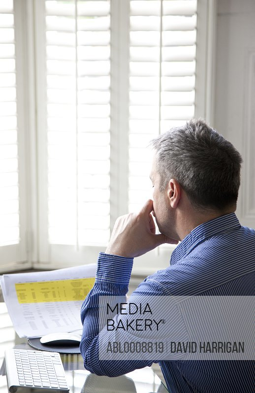 Man Sitting at Desk Looking Over Document