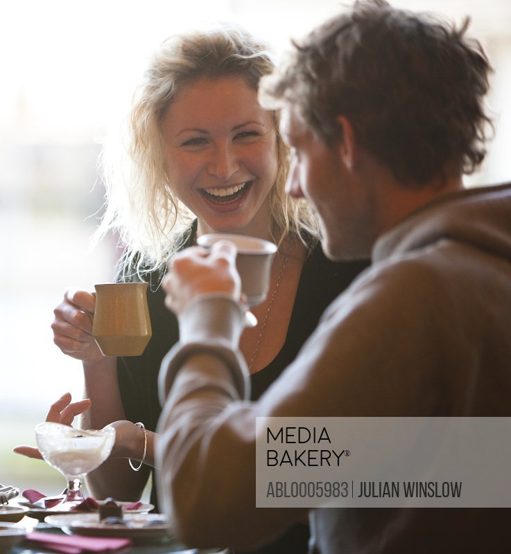 Close up of a young couple sitting in a cafe drinking coffee
