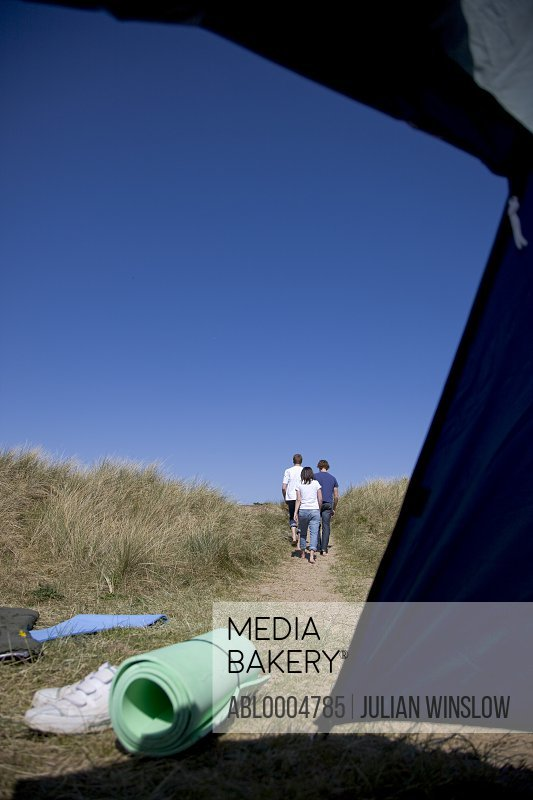 Back of three people walking with tent opening
