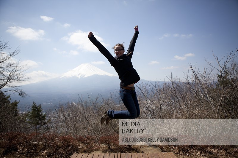 Woman Jumping Mid Air, Mount Fuji in Background