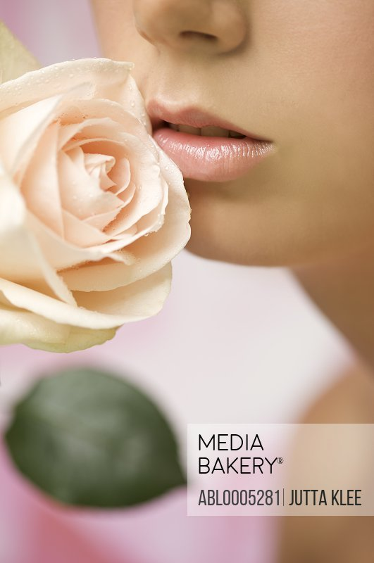 Extreme close up of a young woman inhaling a pink rose - mouth and nose only