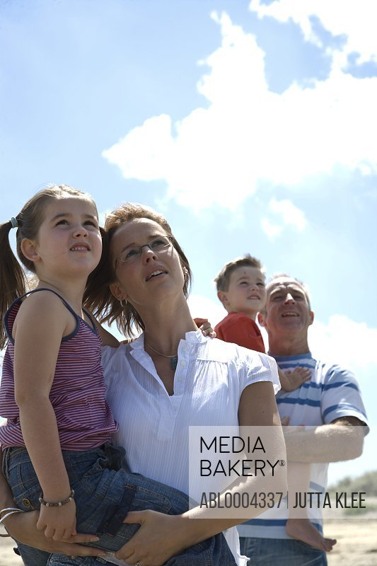 Portrait of young  family looking at sky with interest