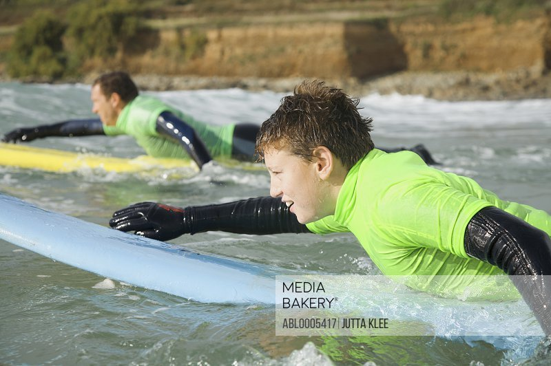 Teenage boy  lying on his surfboard paddling