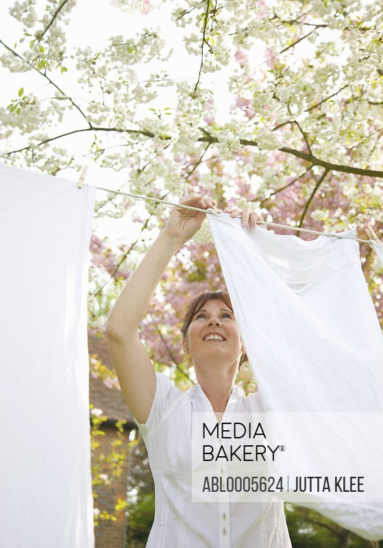 Smiling woman hanging linens on a clothesline