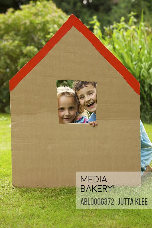 Boy and Girl Looking Out from the Window of Cardboard Cut Out in Shape of House