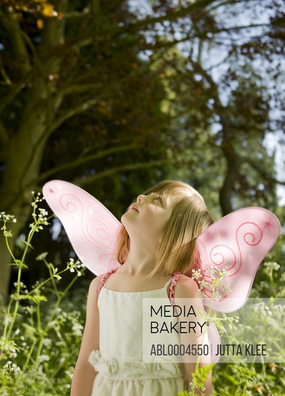 Portrait of a girl in a fairy costume standing in a garden looking up
