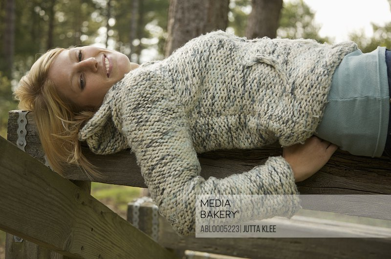 Young woman lying on a wooden beam smiling