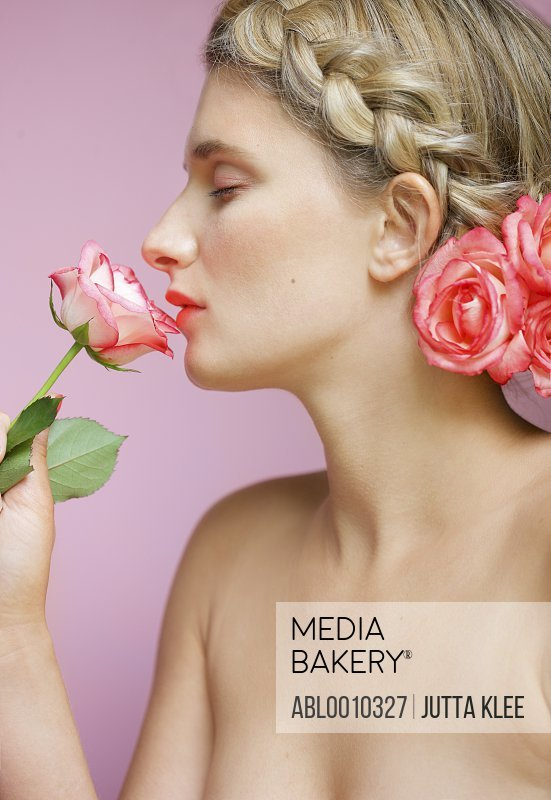 Profile of Young Woman with Braided Hair Smelling Rose