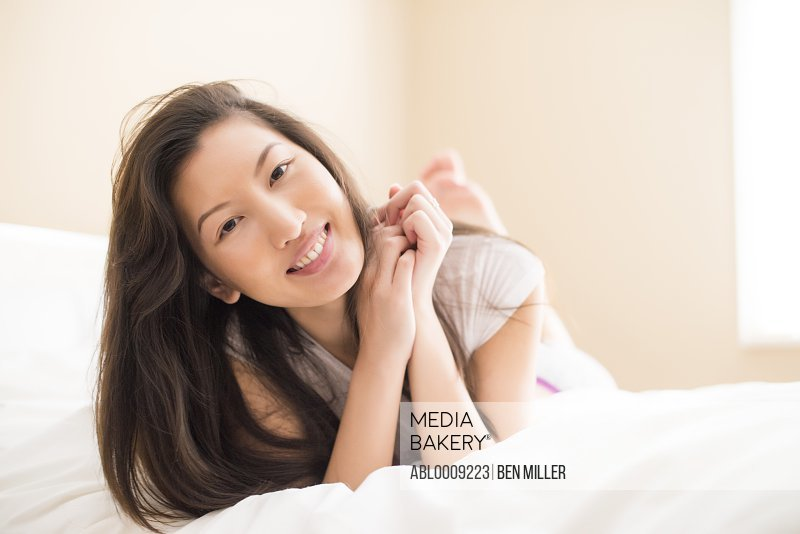 Smiling Woman Lying on Bed