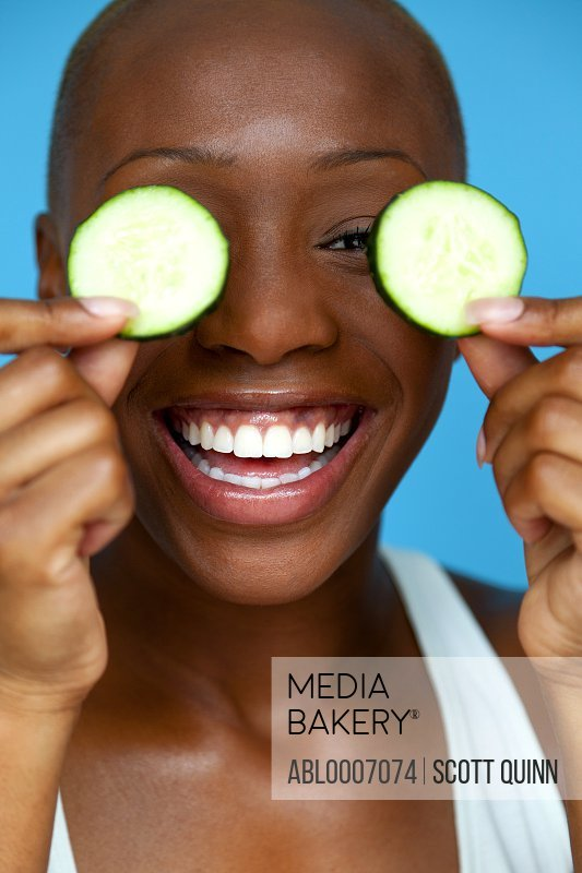 Smiling Woman Holding Cucumber Slices over Eyes