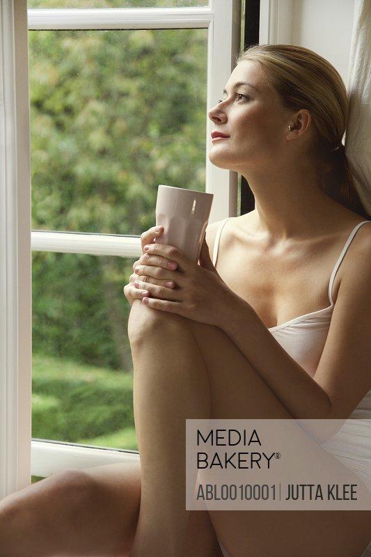 Woman In Underwear Sitting on Window Sill Holding Mug