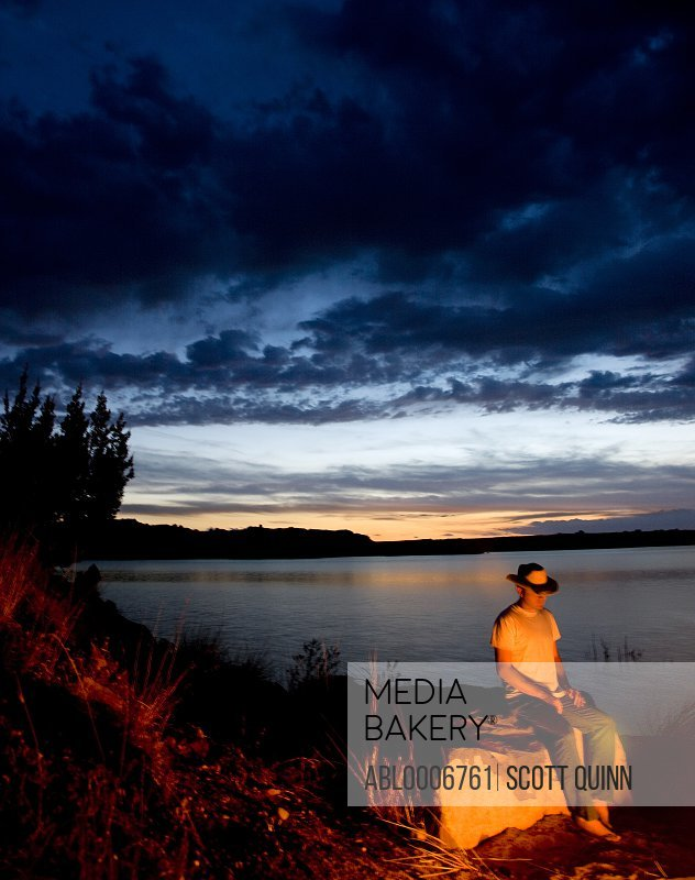 Man Sitting on Rock by River at Sunset