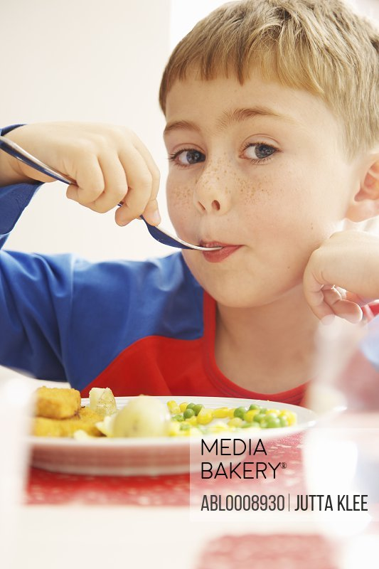 Young Boy Eating Fish fingers and Vegetables