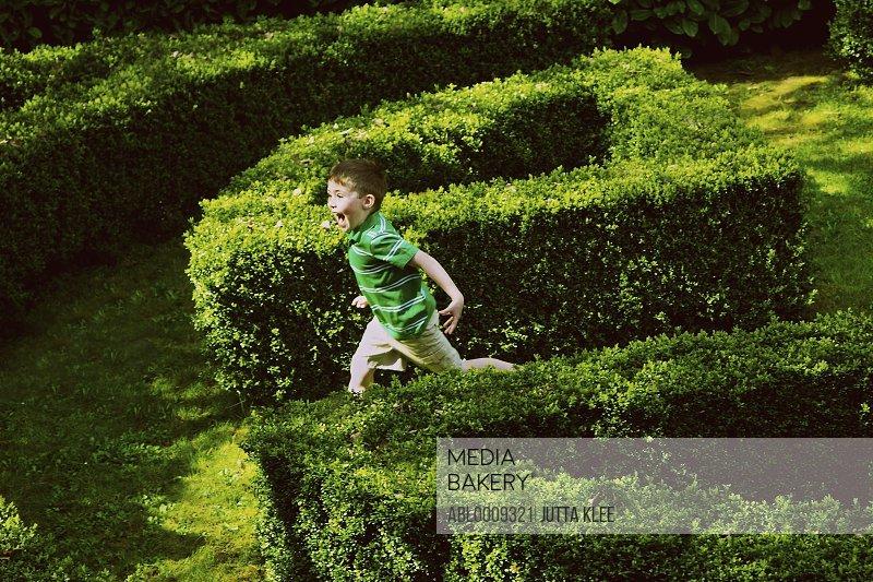 Young Boy Running in Garden Maze