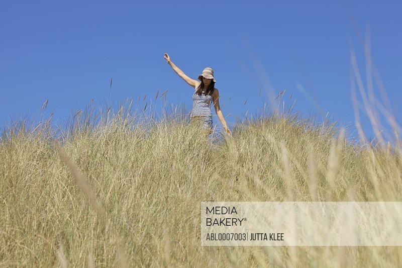 Woman Walking amongst Beach Grass