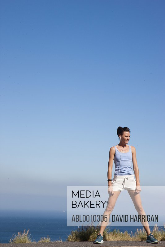 Sport Woman Standing against Ocean and Blue Sky