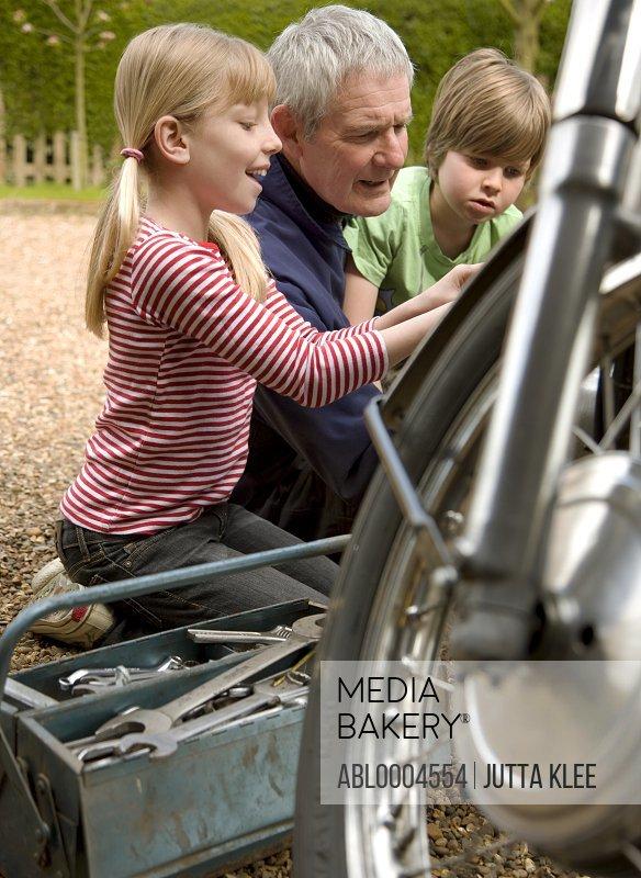 Grandchildren helping grandfather repairing motorbike