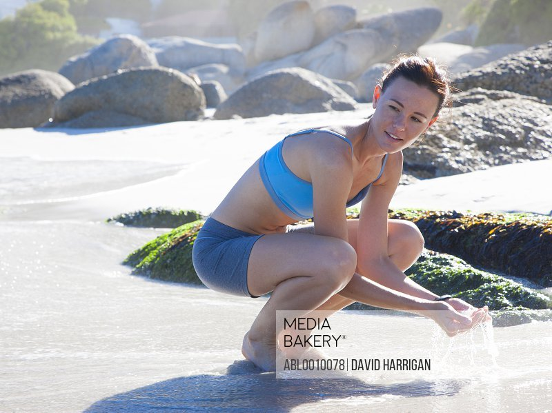Woman Crouching on Beach with Hands Cupping Sea Water