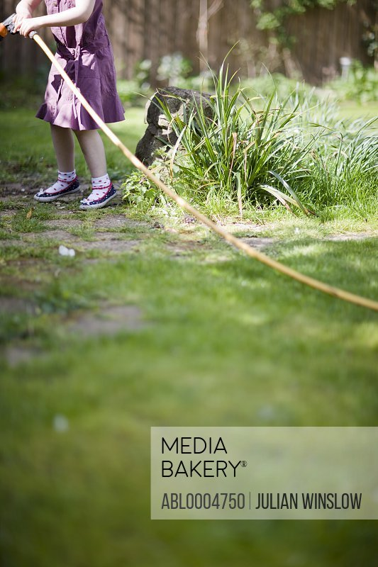 Headless young girl pulling garden hose